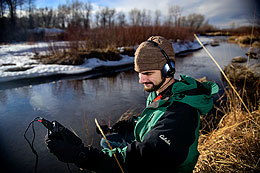 """Jeffrey Santos, a UW senior, records sounds at the Laramie River. Santos, a double major in environmental geology and geohydrology, and environment and natural resources, plans to present a poster presentation, titled """"Voice of the Rivers,"""" during Wyoming Undergraduate Research Day April 26."""